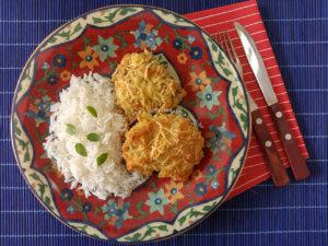 Dois pedaços de frango com crosta de queijo dentro de um prato estampado, acompanhado de arroz branco