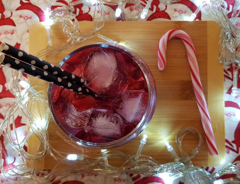 Mesa de Natal montada com uma toalha com estampa de papai noel, uma tábua de madeira clara e luzinhas brancas. Sobre a tábua, um copo com gelo, uma bebida vermelha e canudos.
