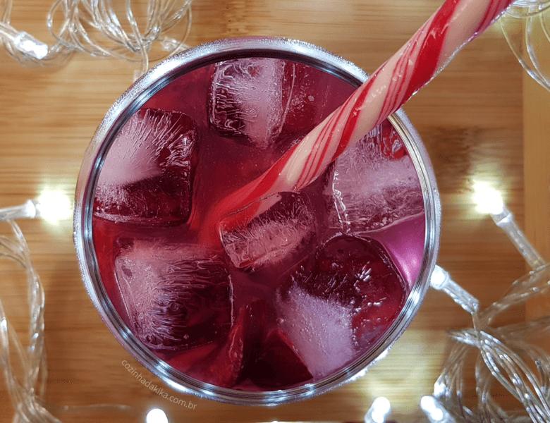 Mesa de Natal montada com  uma tábua de madeira clara e luzinhas brancas. Sobre a tábua, um copo com gelo, uma bebida vermelha um doce em forma de bengala decorando o copo.