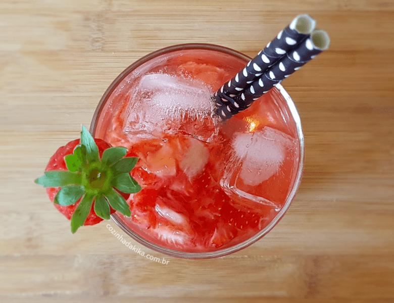 Copo com drink de morango e gelo, decorado com um morango e canudos pretos, sobre uma tábua de madeira.